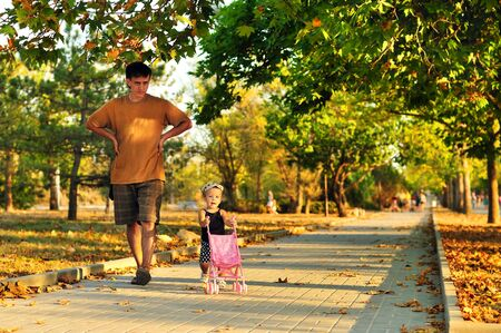 baby stroller: father walking with his baby girl in the park