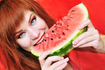 redhead bright girl enjoying sweet watermelon photo