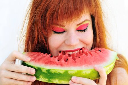 redhead girl enjoying of fresh watermelon photo