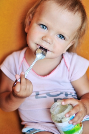 baby girl eating puree from jar on her own  Stock Photo