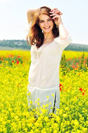 happy beautiful girl on rapeseed field in bloom photo