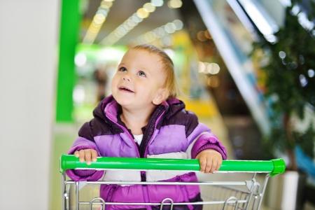 ni�os de compras: beb� feliz sentado en el carrito de la compra Foto de archivo