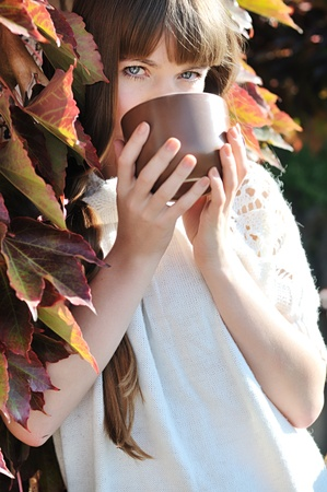 young woman with mug of hot drink outdoors photo