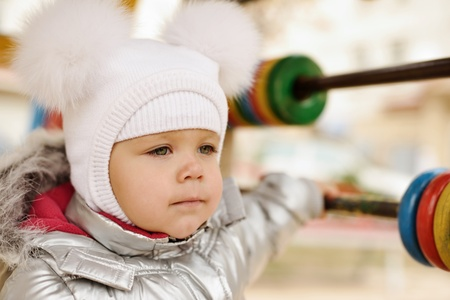 bobble: fashion winter girl wearing fur bobble hat on the playground Stock Photo