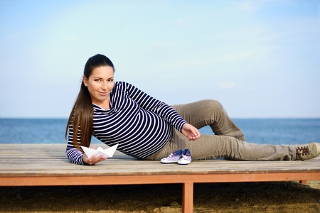 pregnant woman on the beach with paper boat and striped booties photo