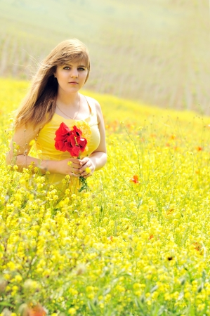 girl with bouquet of poppies in the raps field photo