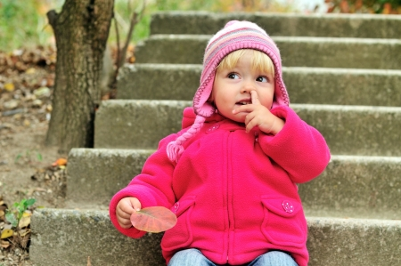 nose picking: baby girl picking her nose outdoors Stock Photo