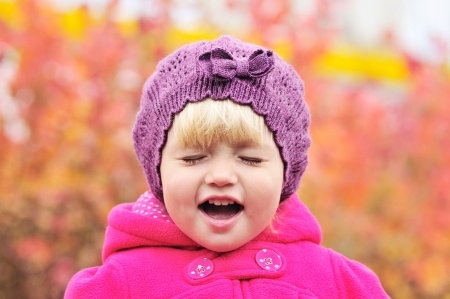 crying toddler girl on over the fall background photo
