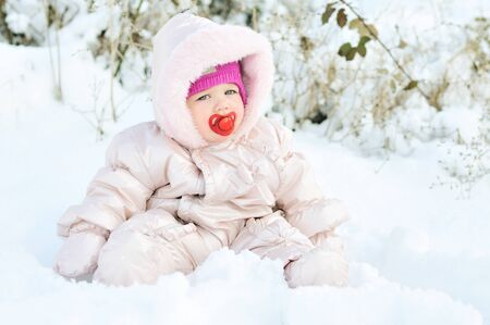 baby girl sitting in snowdrift photo