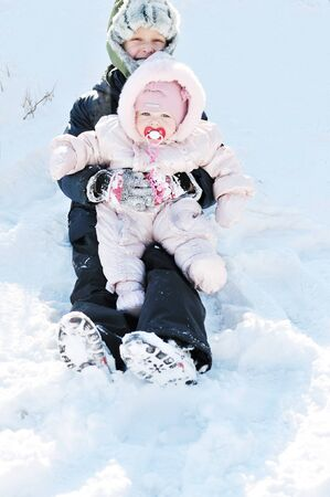 baby girl with brother having fun in snow photo