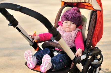 cute baby girl sitting in stroller photo