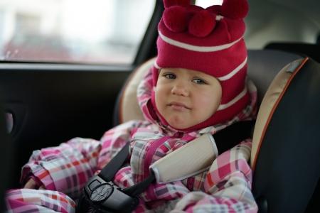 car seat: sad baby girl in car seat in winter time Stock Photo