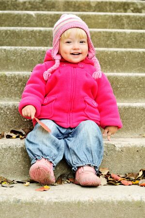 funny toddler sitting on the stairs photo