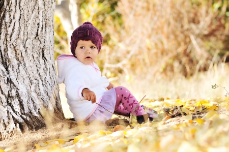 fashion baby girl  sitting under the tree photo