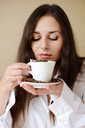 pretty brunette enjoying smell of coffee Stock Photo - 18342296