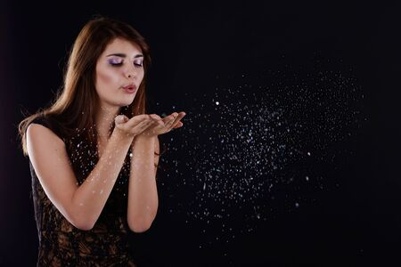 teen girl blowing  snow and  confetti  in studio photo
