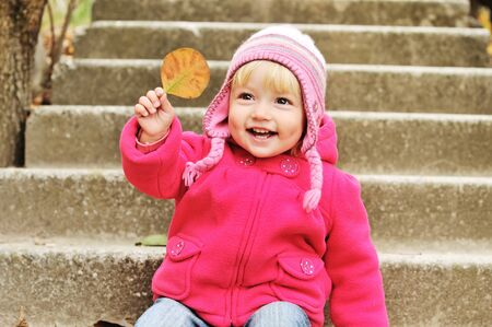 toddler  girl  with leaf on the stairs photo
