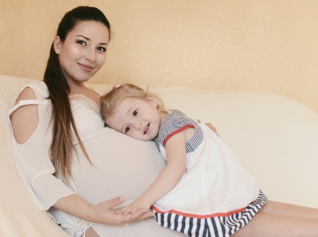pregnant mother with loving daughter in soft selective focus Stock Photo