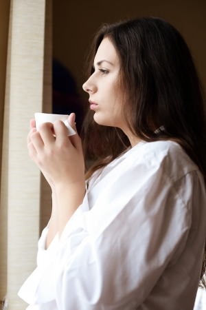 young woman with morning coffee near the window Stock Photo - 18342294