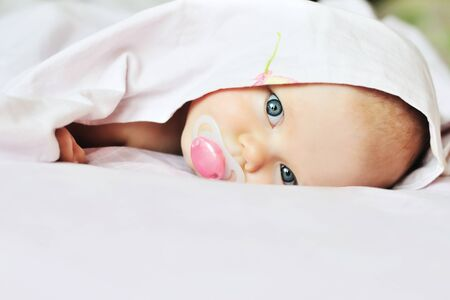 3 monthes old baby looking out under the blanket Stock Photo - 18342116