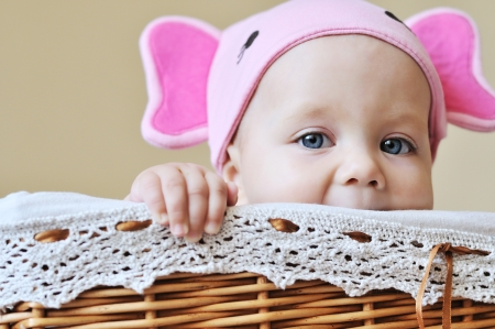 baby in the basket wearing funny hat photo