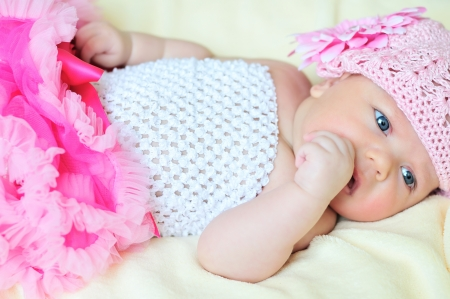 fashion newborn girl with fist in mouth Stock Photo - 18489338