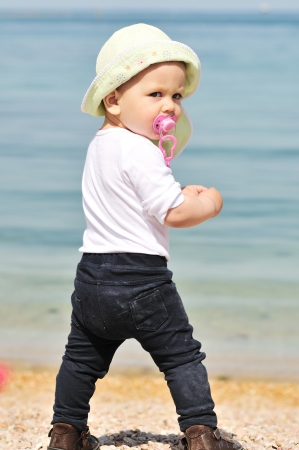 baby girl standing near the sea with dummy photo