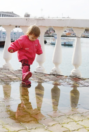 baby girl stepping in puddle on the street photo