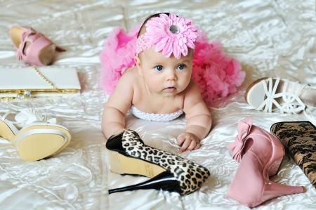 niño modelo: moda niña acostada en la cama con los zapatos de tacón alto y bolsas