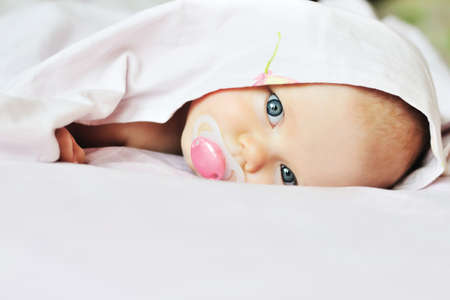 3 monthes old baby looking out under the blanket Stock Photo - 18489076