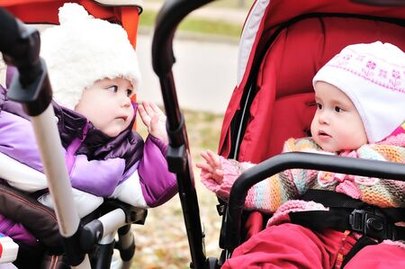 two baby girls sitting in strollers and looking at each  other