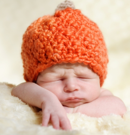 newborn boy wearing pumpkin hat photo