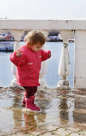 happy childhood of baby girl walking in puddle photo