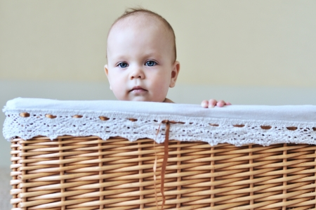 sweet blue-eyed baby in basket  photo