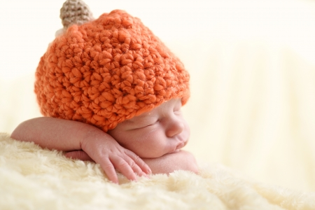sweet  newborn wearing pumpkin hat photo