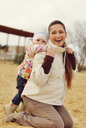 pregnant mother with baby daughter having fun on beach photo
