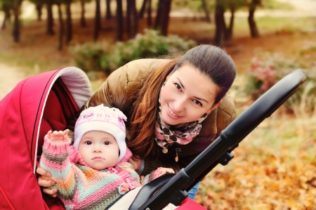 mother walking in the park with her baby in stroller photo