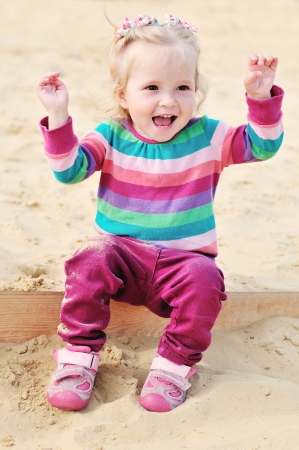happy baby girl  sitting in sandbox photo