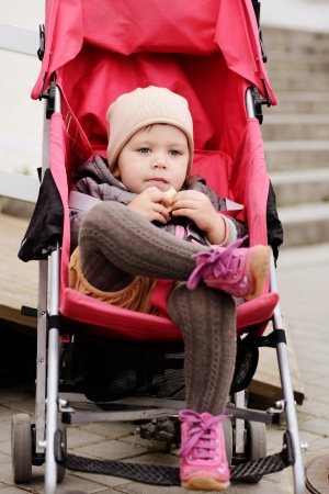 such a cute toddler girl sitting in the stroller photo