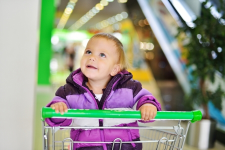 happy lovely baby sitting in shopping trolley photo