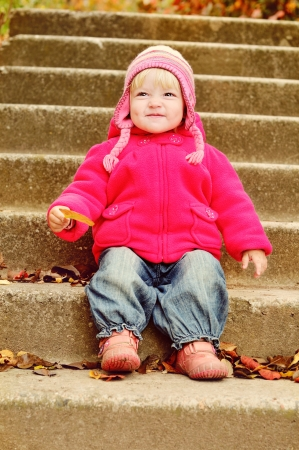 toddler girl with leaf sitting on the stairs photo