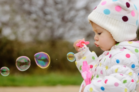 girl with soap bubbles in spring time photo