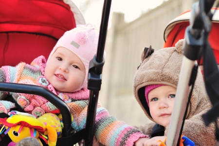 baby carriage: two baby girls sitting in strollers and looking