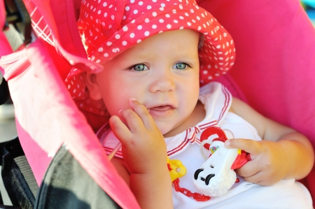 funny baby girl sitting in red stroller photo