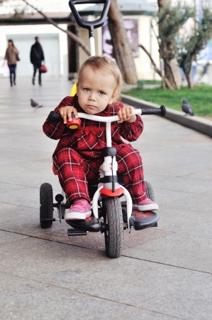 baby girl on her  tricycle on the walk photo