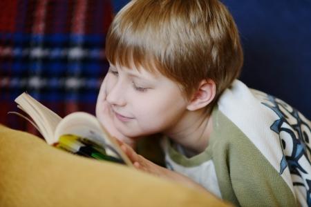 deitado: menino lendo um livro em casa Imagens