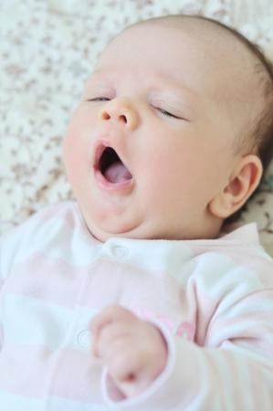 slumbering: baby girl  lying down and yawning Stock Photo