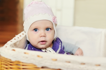 sweet blue-eyed baby  girl in basket photo
