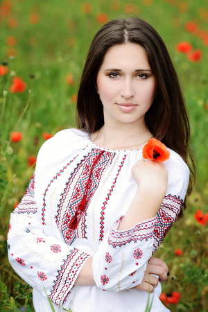 brunette lady with poppy in field  photo