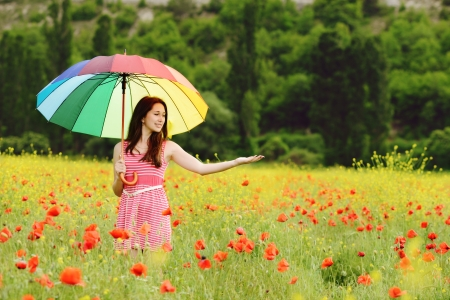 young beautiful girl in poppy field with umbrella photo